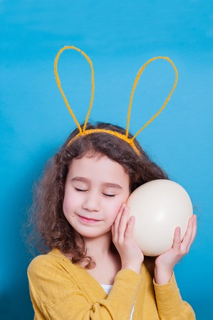 Cheerful little child girl with bunny ears with ostrich egg on a colored background. Happy Easter