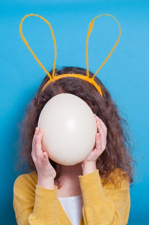 Joyeuse petite fille aux oreilles de lapin avec œuf d'autruche sur fond coloré. Joyeuses Pâques