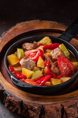 Fried potatoes with meat and vegetables in a pan Stock Photo