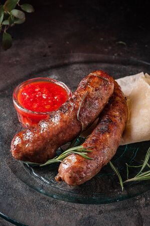Fried domestic sausages with sauce on dark background,selective focus Stock Photo