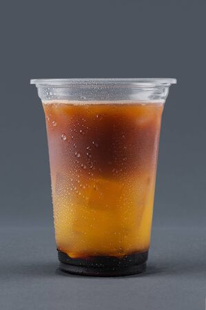 Cold drink with coffee, orange juice and ice cubes on a gray background. Drink in a plastic glass. Takeaway drink. Glass with drops