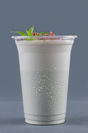 Milkshake with mint and chocolate chips on a gray background. Drink in a plastic glass. Takeaway drink. Glass with drops