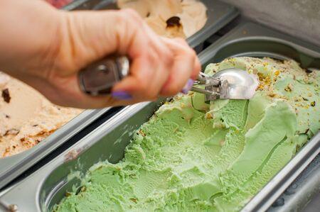 Woman dials a ball of ice cream. Scooping pistachio ice cream. Selective focus