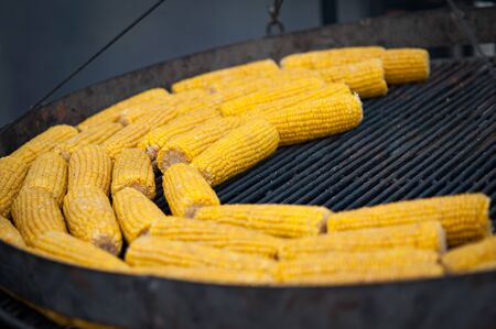 Grilled corn. Street food festival. Close up of appetizing grilled sweet corn on the bbq grill. Selective focus