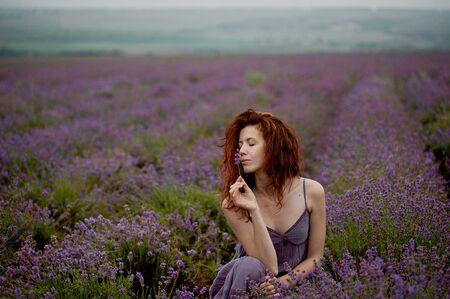 Red hair girl in lavender field in rainy day 写真素材 - 143228455