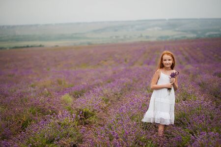 Cute red-haired girl in lavender field in rainy day 写真素材 - 143228457