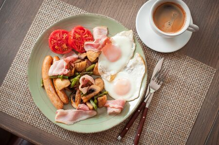 Fried eggs with bacon, sausages, vegetables and a cup of coffee. Top view
