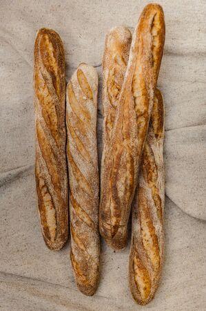 Buckwheat baguettes in baker's hands. Gluten free. Soft focus