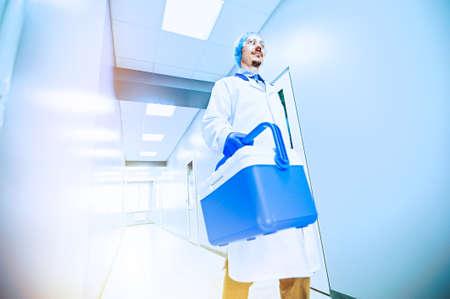 Medical worker, nurse, doctor holding a portable refrigerator bag in the hospital. Foto de archivo