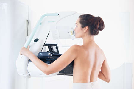 Young woman at breast cancer prevention screening at hospital. Hardware examination of the breast. Healthy young woman doing cancer prophylactic mammography scan. Modern hospital with hi-tech machine Stock Photo