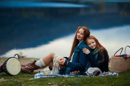 A young woman and a girl with red long hair sitting on a blanket in autumn. Boho style