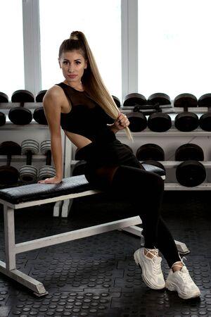 Attraktive Fitness-Frau auf Fitness-Hintergrund, trainierter weiblicher Körper, Lifestyle-Porträt, kaukasisches Modell, Fitness-Mädchen trainiert mit Hantel, gesundes Lifestyle-Konzept