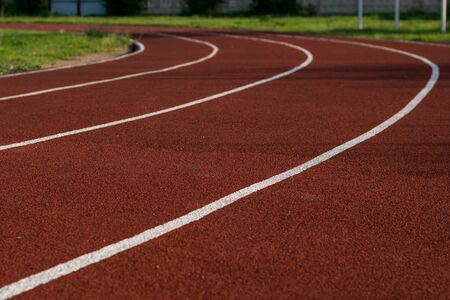 Running track in the stadium. Rubber coating. Treadmill in the fresh air. Healthy lifestyle concept. Athletes cardio workout.