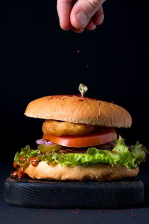 chicken fingers: Homemade chicken burger with onion, pickles, fresh vegetables, tomato sauce on serving dark wooden board and mans fingers sprinkling pepper on top of it. Black background, selective focus, vertical composition Stock Photo