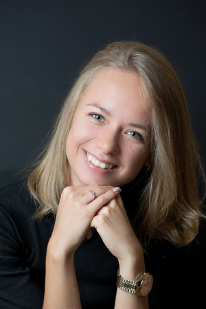 Portrait of young blond lady in black T-shirt smiling with teeth and holding her chin on her hands Reklamní fotografie