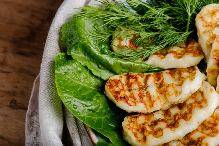 Grilled homemade halumi cheese with fresh green herbs over wooden background, top view, close-up