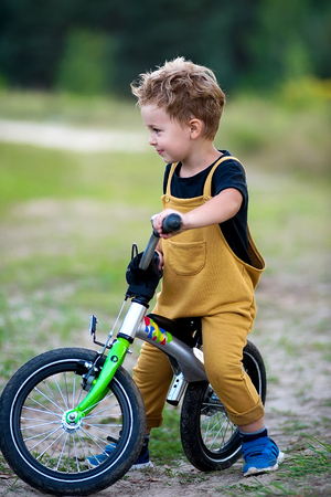 Cute little boy in yellow overall going with bicycle and smiling on summer day in countryside Stock Photo