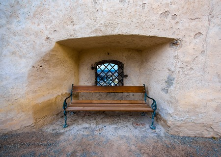 lattice window: Wooden bench and window in ancient stone wall, Salzburg