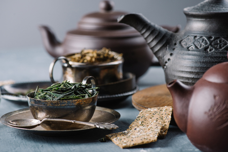 Dry green tea in bowl, crispy bread slices and clay teapots