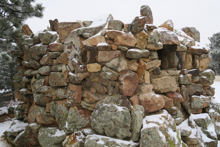 Pile of stones with windows or small fortress with battlements after snowfall in mountains