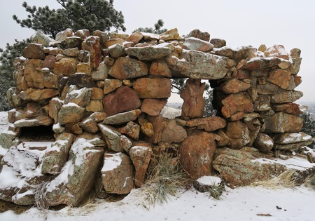 Pile of stones placed as wall with windows or battlements of fortress after snowfall in mountains