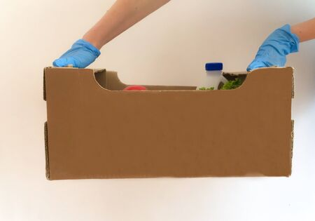 male hands in blue gloves hold a cardboard box with products, a grocery store delivery man, fresh products - milk, fruits, lettuce, food