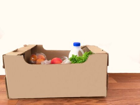 delivery of products for online shopping in a cardboard box - milk, fruit, food