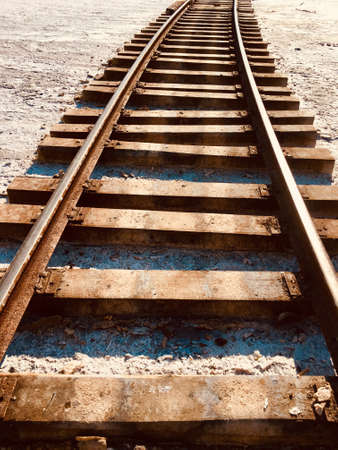 sleepers and rails run along the ground that is covered with white salt Banque d'images