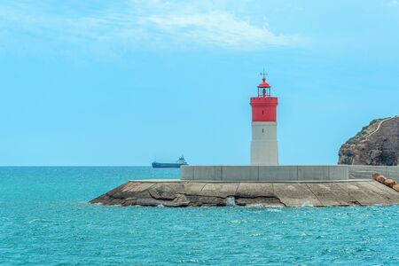 Red and white lighthouse at sea and ship on the horizon near The city of Cartagena, Spain.