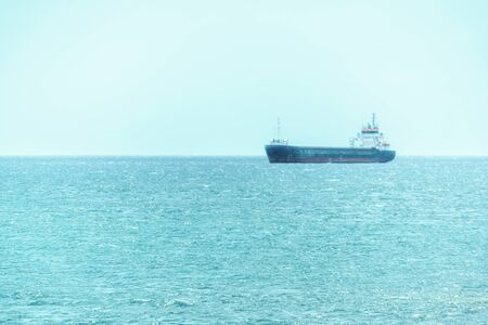 Blue water and transport ship in the sea on the horizon Foto de archivo
