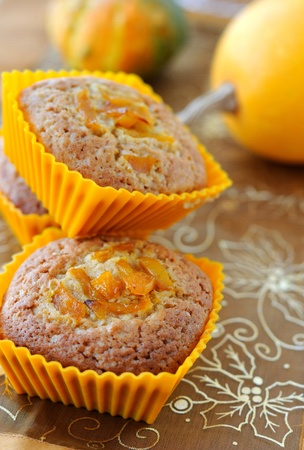 Sweet pumpkin muffins in сupcakes decorated with caramelized pumpkin. Stock Photo