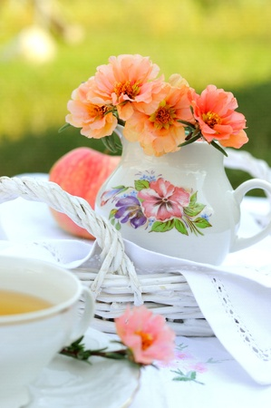 Still life with flowers in a jug and a cup of tea. Stock Photo