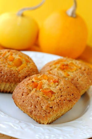 Pumpkin muffins with a pair of pumpkins at the background.
