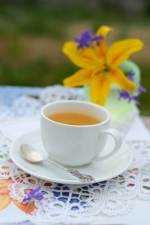 Сup of tea with a lily on a background photo