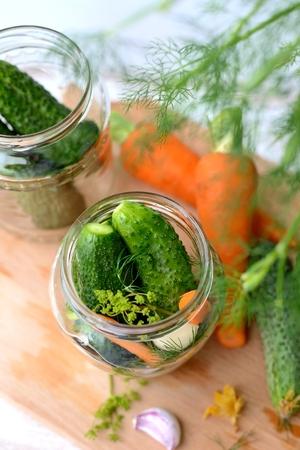 distributing: Distributing cucumbers between jars to prepare pickling ones