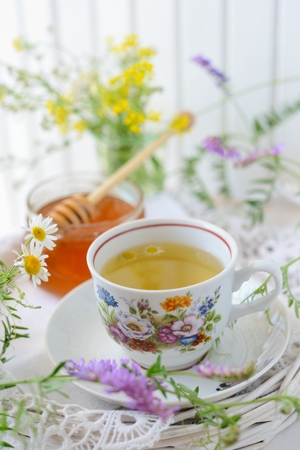 A summer cottage table wildflower, tea and honey  photo