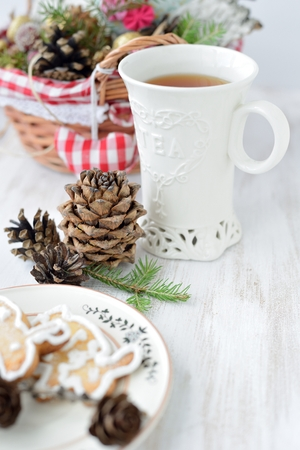 Christmas composition with a cup of tea, fir cones and cookies  photo