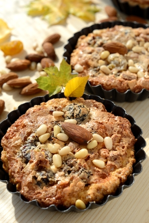 Small tarts in metal shapes, shells filled with nuts and raisins, decorated with pine nuts and almonds  photo