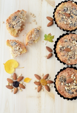 Autumn still life of nut pastries and autumn leaves   Small tarts in metal shapes, shells filled with nuts and raisins, decorated with pine nuts and almonds  photo