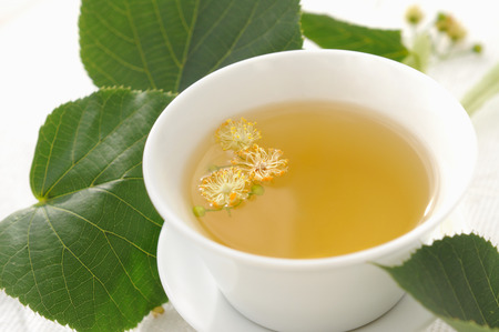linden tea: White cup  full of linden tea.