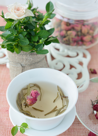 afternoon tea: Cup of healthy green tea with dried roses Stock Photo