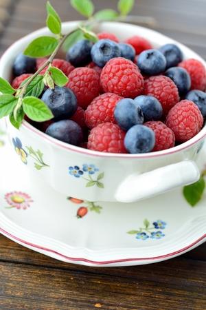 A bowl of fresh raspberries and blueberries