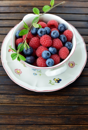 A bowl of fresh raspberries and blueberries