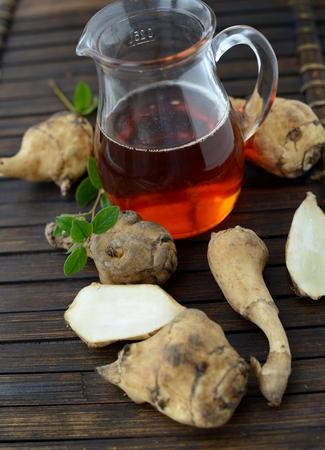 Jerusalem artichoke and jerusalem artichoke syrup on a wooden table Stock Photo