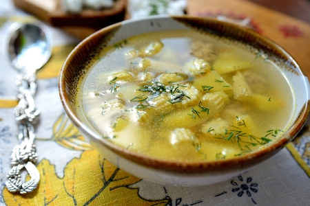 A bowl of soup with corn and other vegetables