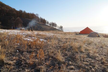 On a slope covered with last year's dry grass, there are red and khaki tourist tents. table with dishes and smoke from the fire.on the background of a high Bank descending to the surface of the lake covered with ice