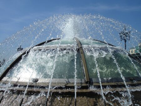 Jets of water from the fountain tend to the blue sky and flow down the glass dome