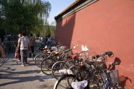 people walk along the sidewalk near the bike Park near the old, terracotta wall. on one of the bikes, gloves are attached to the handlebars.