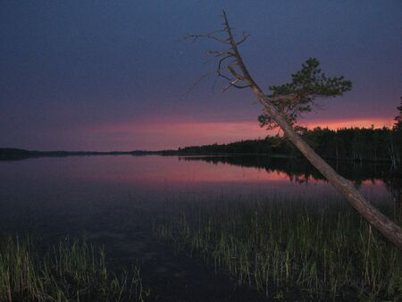 night view of the dark lake and the sky painted in the maroon colors of the sunset