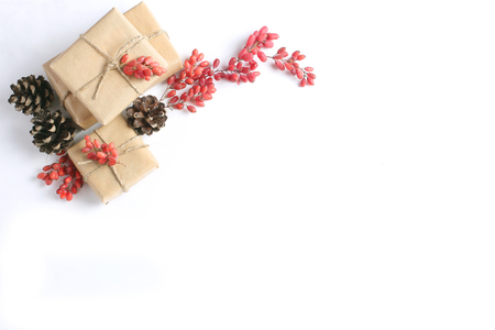 New Years composition from gifts wrapped with kraft paper, cones and berries on a white background. Flat lay, top view Stock Photo